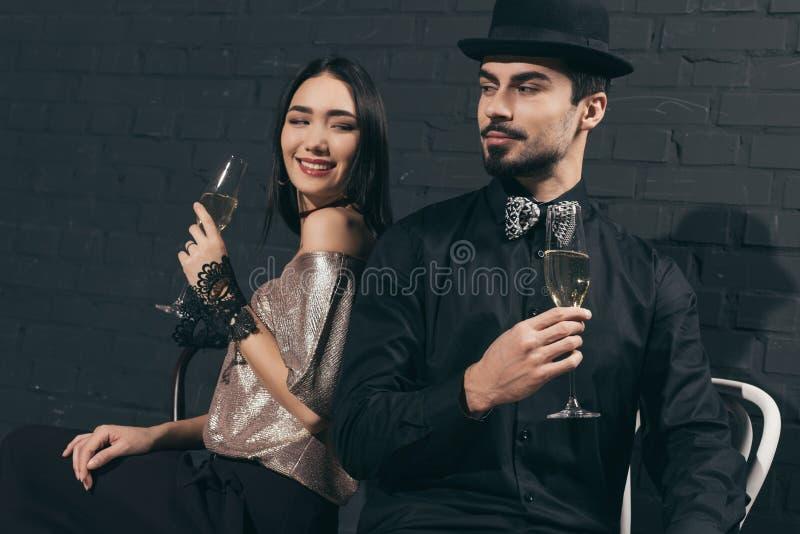 stående av stilfulla mångkulturella par med exponeringsglas av champagne fotografering för bildbyråer