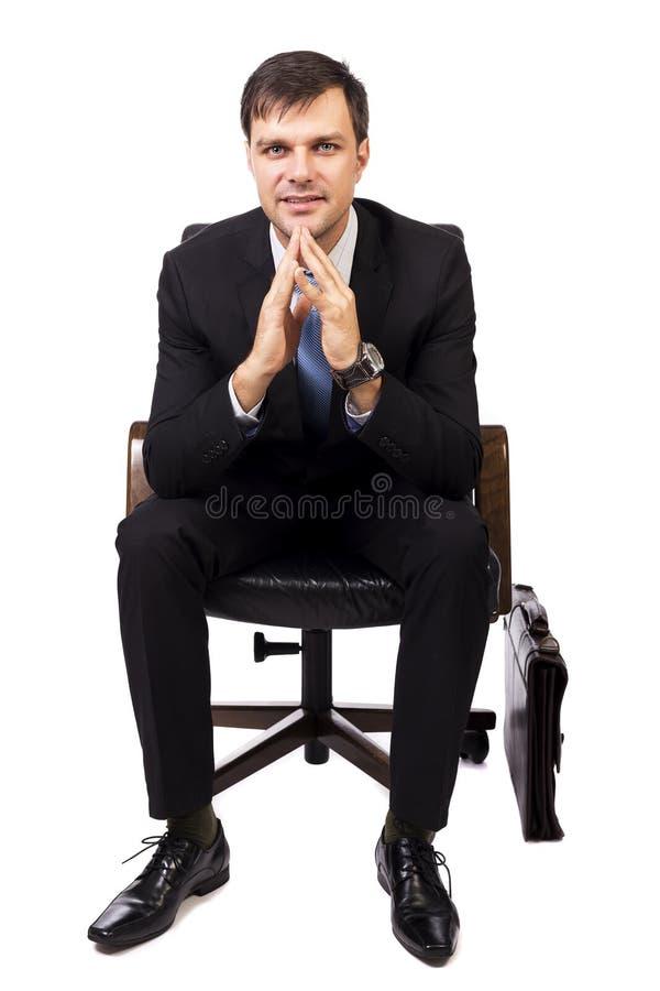 Stående av stiligt ungt affärsmansammanträde på stol fotografering för bildbyråer