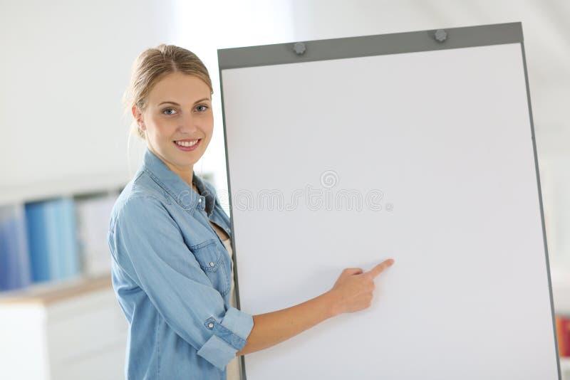 Stående av studenten i klassrum som pekar fingret på tomt bräde arkivbilder