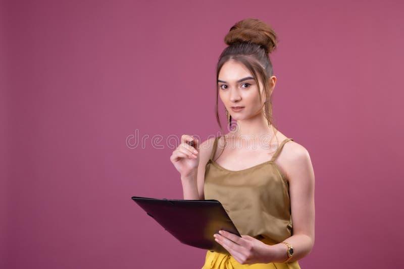 Stående av studentflickan med penn- och pappersmappen Ung n?tt arbetarhandstil n?got i henne legitimationshandlingar arkivbild
