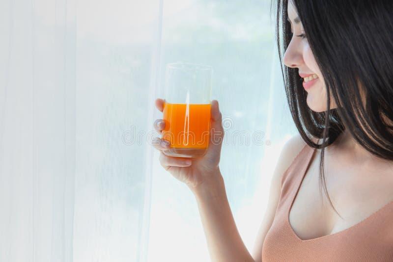 Stående av sund dricka ny orange fruktsaft för ung asiatisk kvinna av exponeringsglas royaltyfria foton