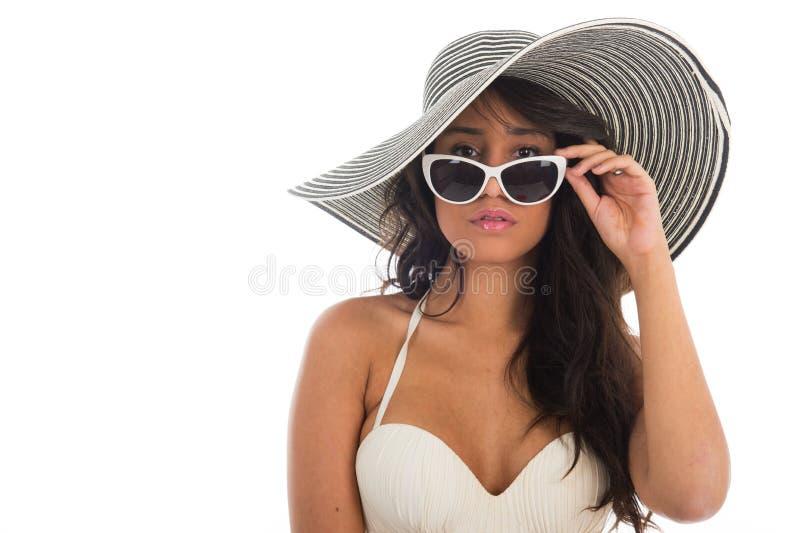 Stående av svarta kvinnan i den vita bikinin med sugrörhatten arkivfoto