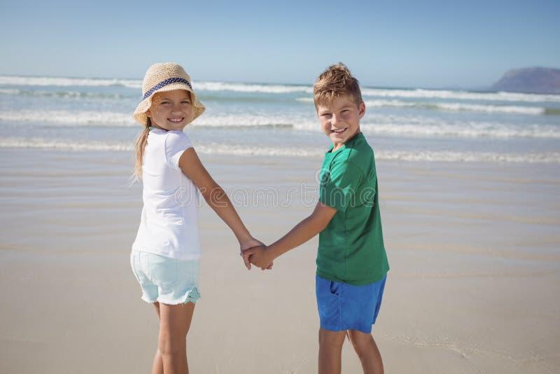 Stående av syskon som rymmer händer på kust på stranden arkivfoton