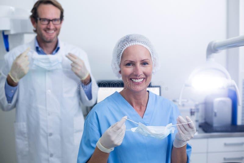 Stående av tandläkaren och den tand- assistenten som bär den kirurgiska maskeringen arkivbild