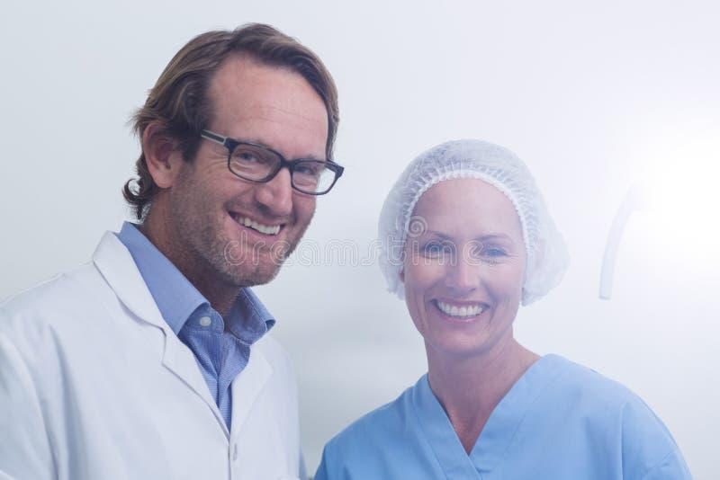 Stående av tandläkaren och den tand- assistenten som bär den kirurgiska maskeringen royaltyfri fotografi