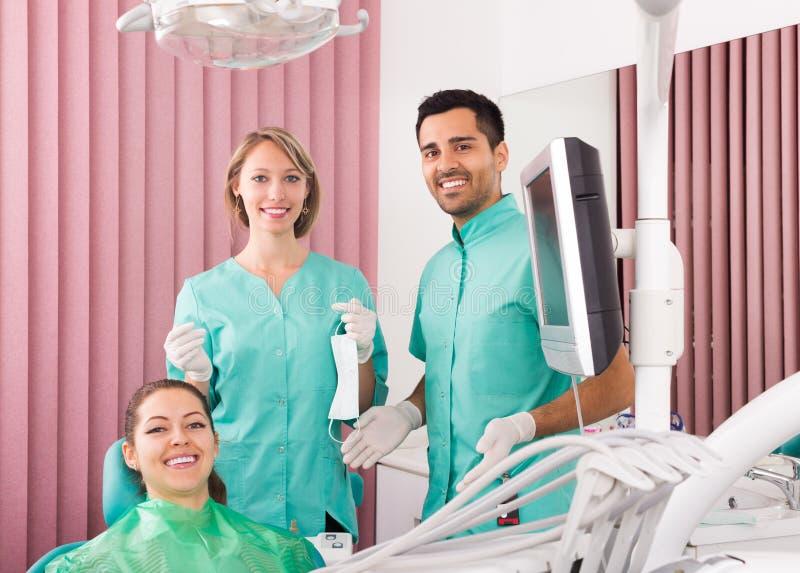 Stående av tandläkaren och patienten på den tand- kliniken arkivfoton
