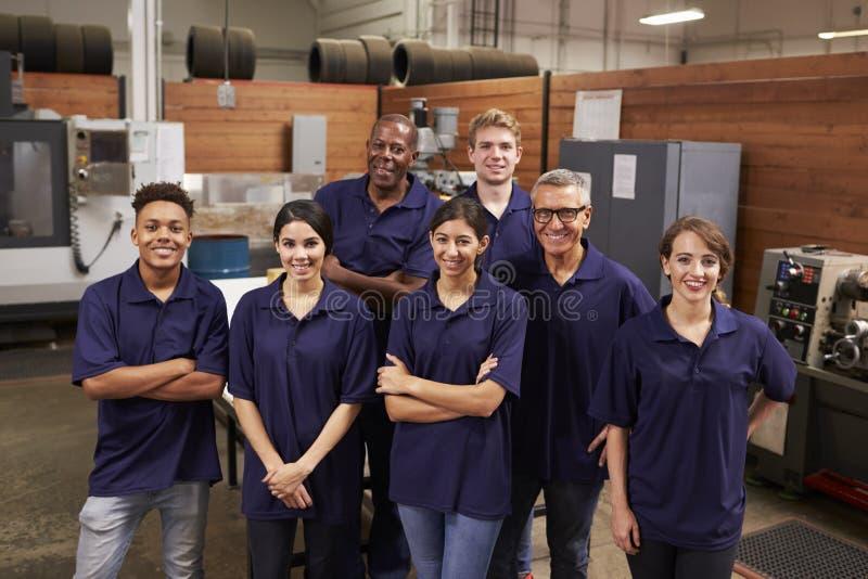 Stående av teknikerer och lärlingar i upptagen fabrik arkivfoto