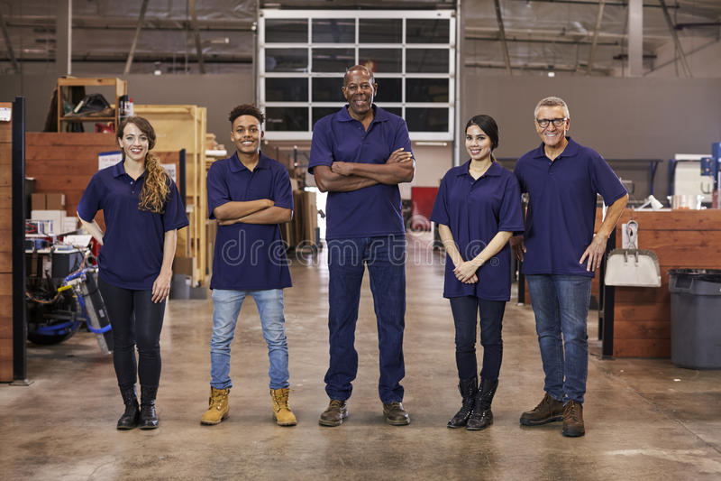 Stående av teknikerer och lärlingar i upptagen fabrik arkivbild