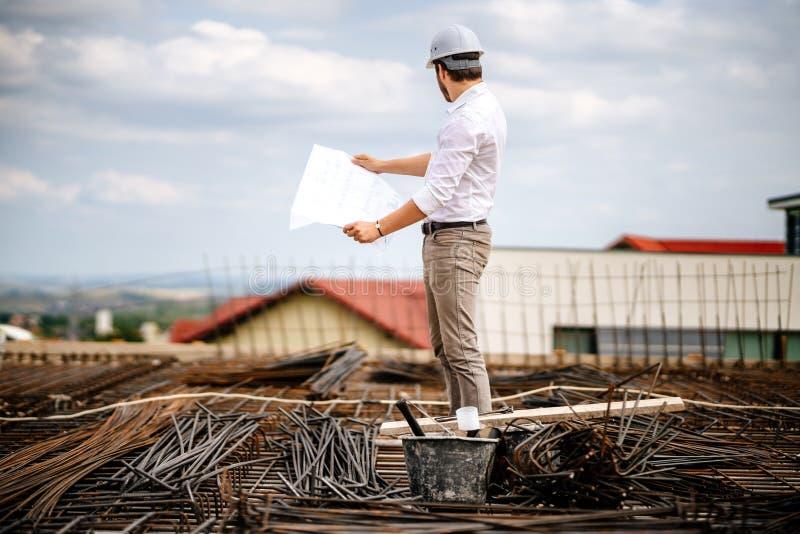 Stående av teknikern som ser pappers- plan, konstruktionsritningar arkivbilder