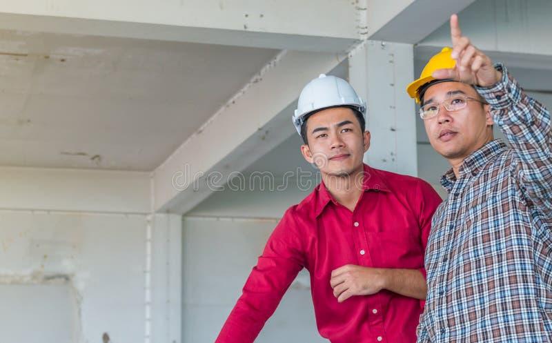Stående av teknikern som talar om konstruktionsjobb med förpliktelse till framgång på konstruktionsplatsen arkivbilder