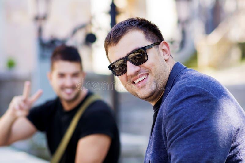 Stående av till härliga unga män som ler på gatan arkivfoton