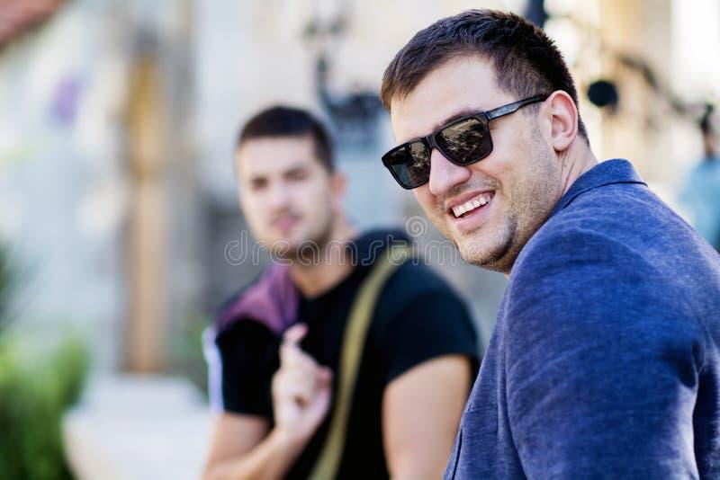 Stående av till härliga unga män som ler på gatan arkivbilder