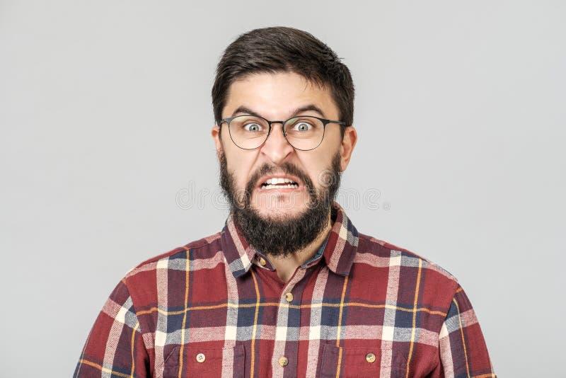 Stående av tokig ilsken ung manlig ilska och raseri p? gray arkivfoto
