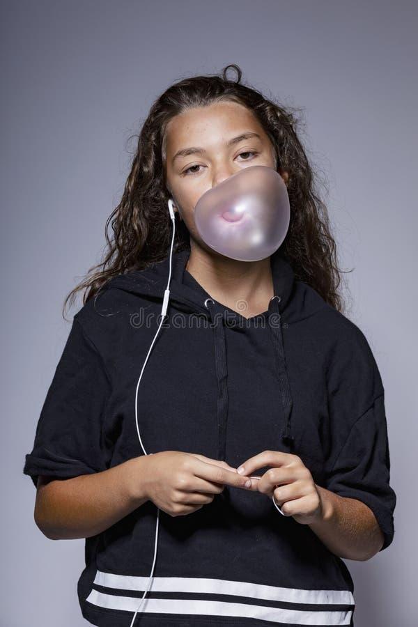 Stående av tonårigt med exponeringsglas i studion, medan spela med ett tuggummi royaltyfri bild