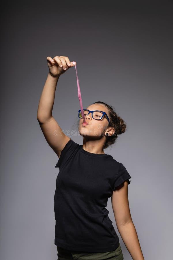 Stående av tonårigt med exponeringsglas i studion, medan spela med ett tuggummi royaltyfria foton