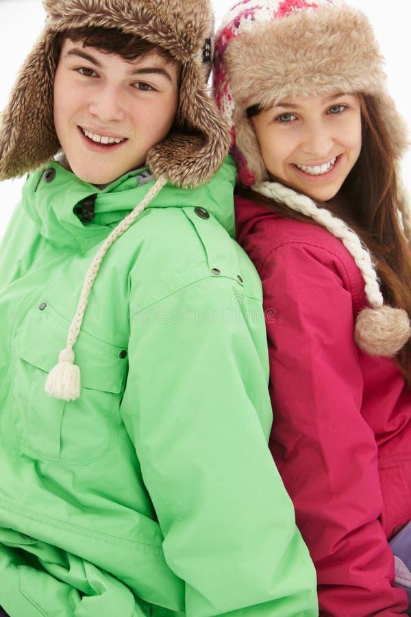 Stående av tonårs- par i Snow royaltyfri fotografi