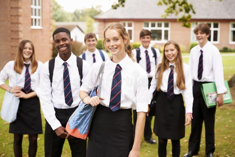 Stående av tonårs- studenter i enhetliga utvändiga skolabyggnader arkivfoton