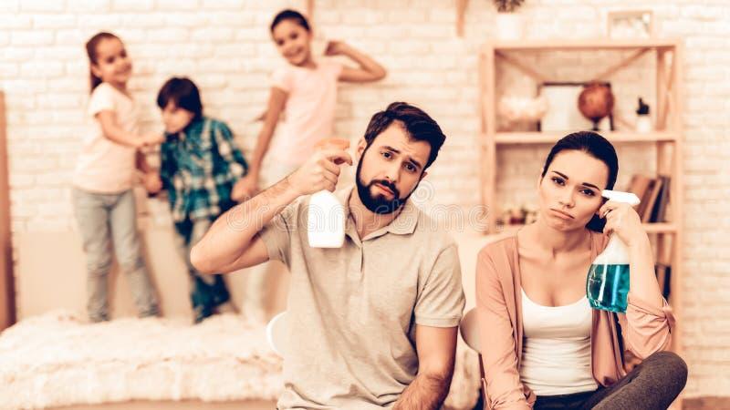 Stående av trötta föräldrar, når att ha gjort ren hemmet arkivfoto