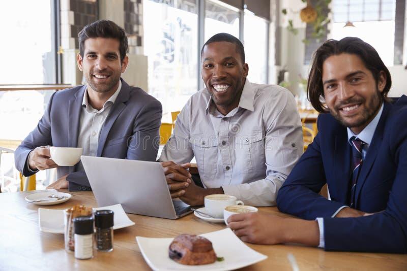 Stående av tre affärsmän som har möte i coffee shop arkivbild