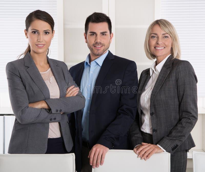 Stående av tre affärspersoner: man och kvinna i ett lag arkivfoton