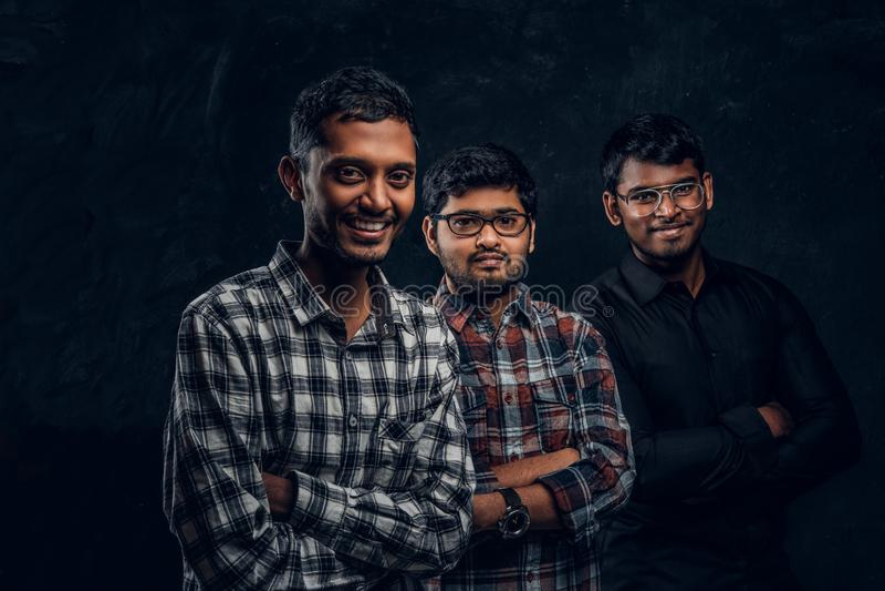 Stående av tre indiska studenter som bär tillfällig kläder mot en mörk texturerad vägg arkivfoton