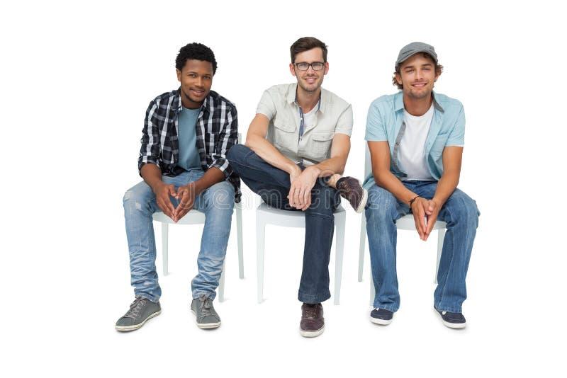 Stående av tre kalla unga män som sitter på stolar royaltyfri bild