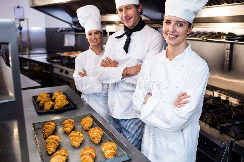 Stående av tre kockar i kommersiellt kök arkivfoton
