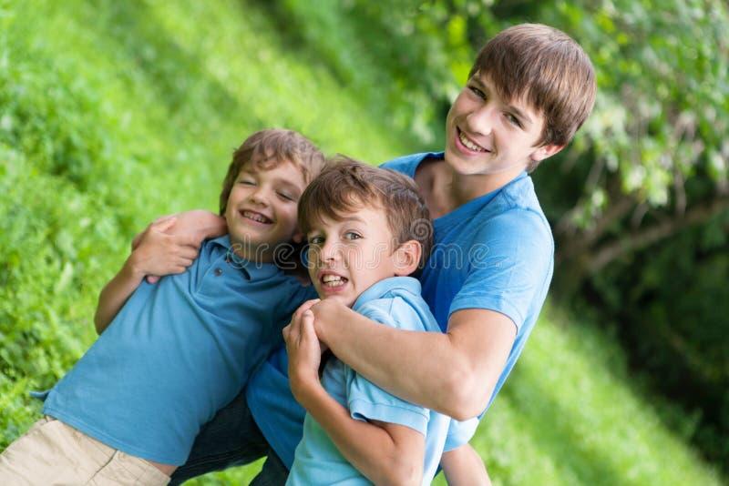 Stående av tre lyckliga bröder arkivfoton