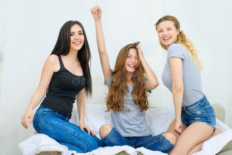 Stående av tre lyckliga nätta unga kvinnor hemma arkivbild