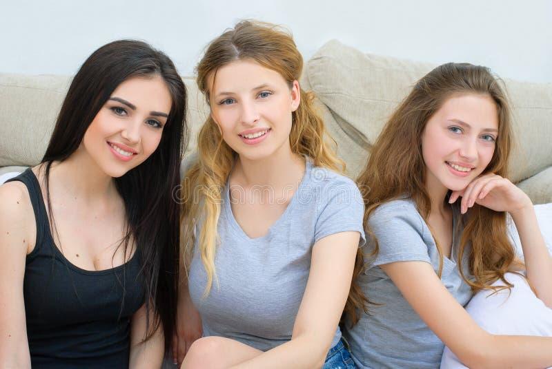 Stående av tre lyckliga nätta unga kvinnor hemma arkivfoto