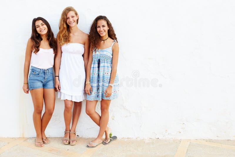 Stående av tre tonårs- flickor som lutar mot väggen royaltyfri fotografi
