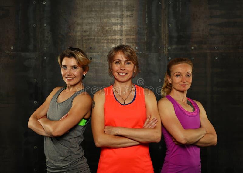 Stående av tre unga idrotts- kvinnor i idrottshall royaltyfria bilder