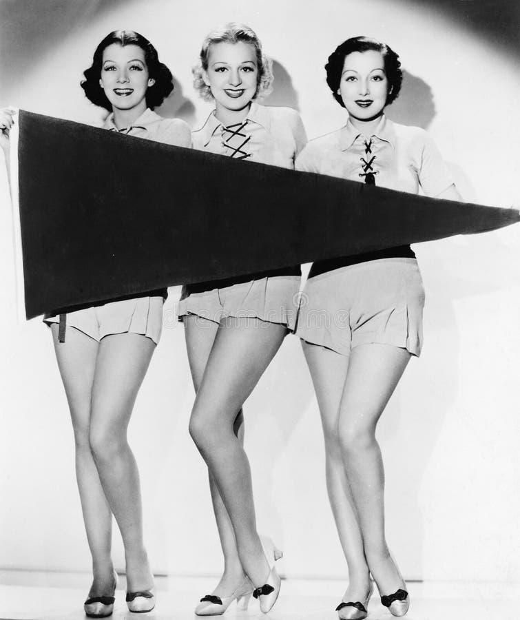 Stående av tre unga kvinnor som rymmer ett baner och le (alla visade personer inte är längre uppehälle, och inget gods finns supp arkivbilder