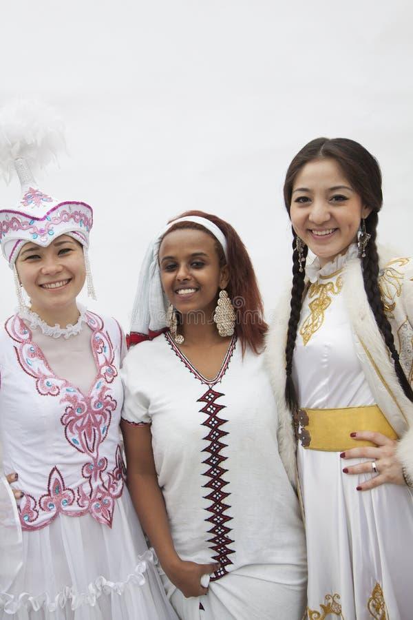 Stående av tre unga mång--person som tillhör en etnisk minoritet kvinnor i deras traditionella kläder, studioskott royaltyfri bild
