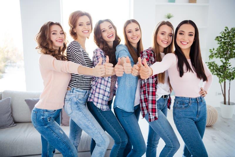 Stående av trevliga charmiga attraktiva gladlynta glade lyckade damer som ger sig visa rådgivning för thumbupannonsannons glat br royaltyfri fotografi