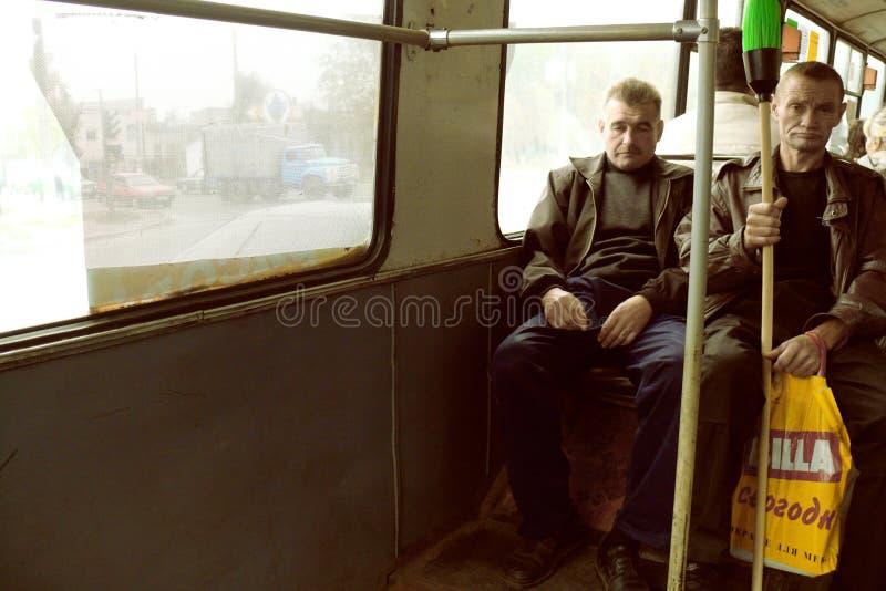 Stående av två arbetarklassmän som pendlar i buss arkivbild
