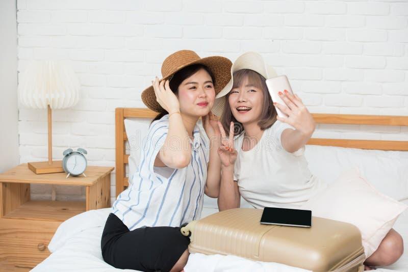 Stående av två asia lyckliga härliga unga flickor som direktanslutet gör selfie på säng efter fullföljandebokninglopp royaltyfria foton