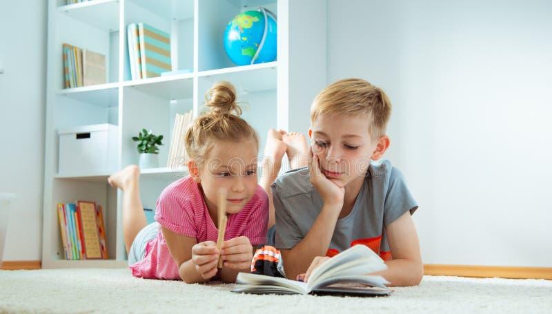 Stående av två barn som hemma läser en bok på golvet arkivbilder