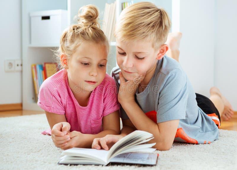 Stående av två barn som hemma läser en bok på golvet royaltyfria foton