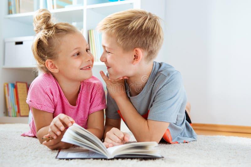 Stående av två barn som hemma läser en bok på golvet arkivbild