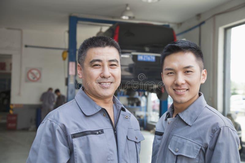 Stående av två garagemekaniker fotografering för bildbyråer