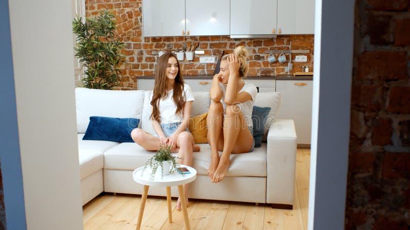 Stående av två gladlynta tonårs- flickvänner som hemma kopplar av royaltyfria foton