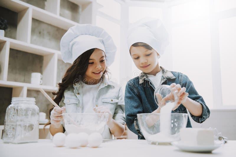 Stående av två gulliga barn som lagar mat på kök arkivbilder