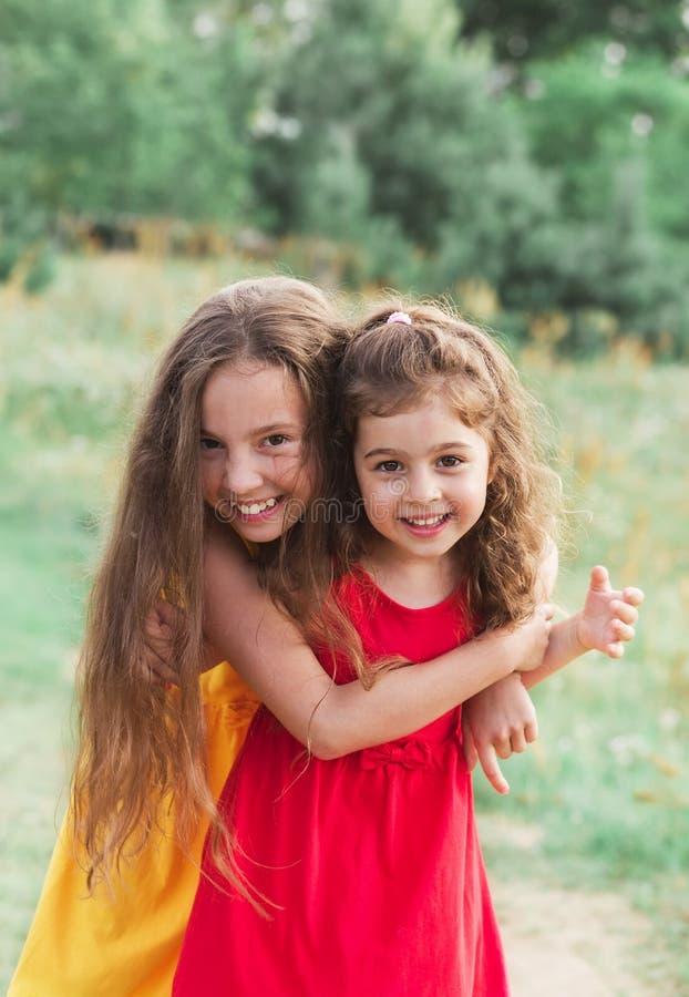 Stående av två gulliga små flickor som omfamnar och skrattar på bygden lyckliga ungar utomhus royaltyfri fotografi