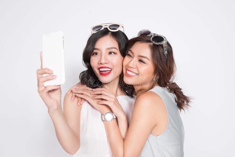 Stående av två härliga asiatiska trendiga kvinnor som tar selfie royaltyfria bilder