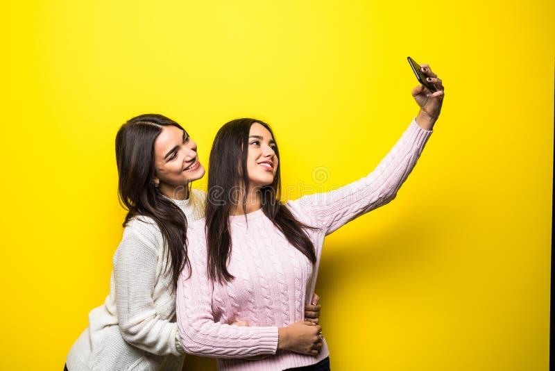 Stående av två iklädda tröjor för älskvärda flickor som står och tar en selfie över gul bakgrund arkivbilder