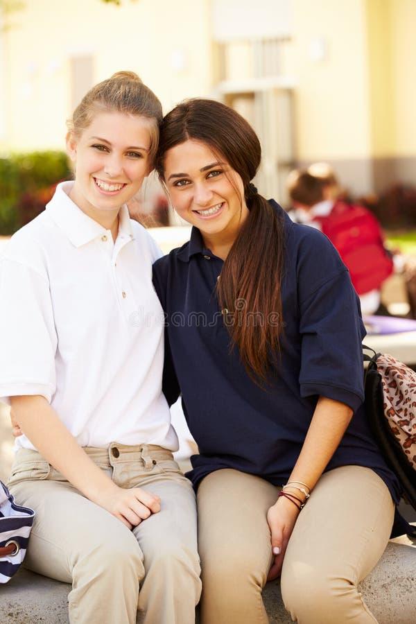 Stående av två kvinnliga högstadiumstudenter som bär likformign arkivbilder