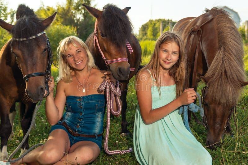 Stående av två kvinnor i natur med hästar royaltyfri bild