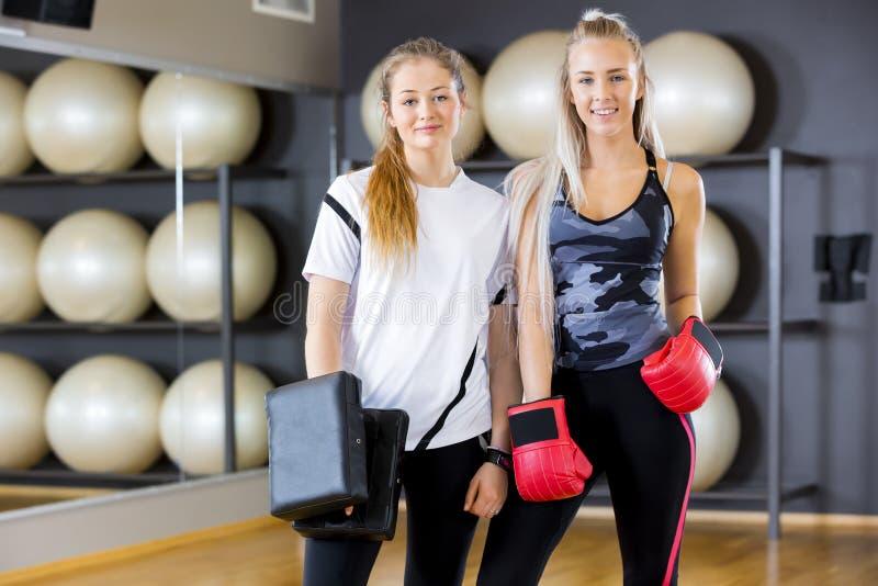 Stående av två kvinnor på boxningutbildning i konditionidrottshall fotografering för bildbyråer