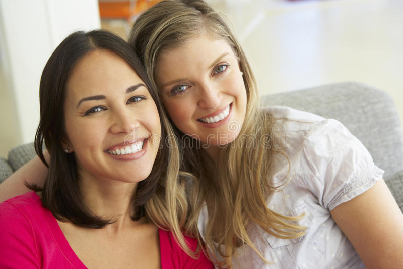 Stående av två le kvinnliga vänner på soffan royaltyfri foto